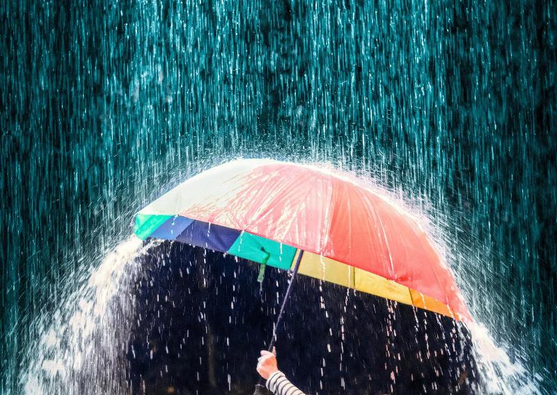 Sataa paljon vettä, keskellä käsi joka pitää sateenvarjoa.
