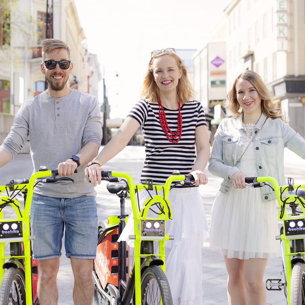 Kolme nuorta aikuista Kuopion kaupungin VILKKU-sähköpyörien kera.